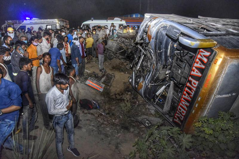 Un grupo de gente rodea los restos de un bus que transportaba a trabajadores migrantes tras el alivio de las restricciones contra el coronavirus, luego de chocar contra una camioneta de reparto en una carretera cerca de Kanpur, en el estado de Uttar Pradesh, en India, el 8 de junio de 2021. (AP Foto)
